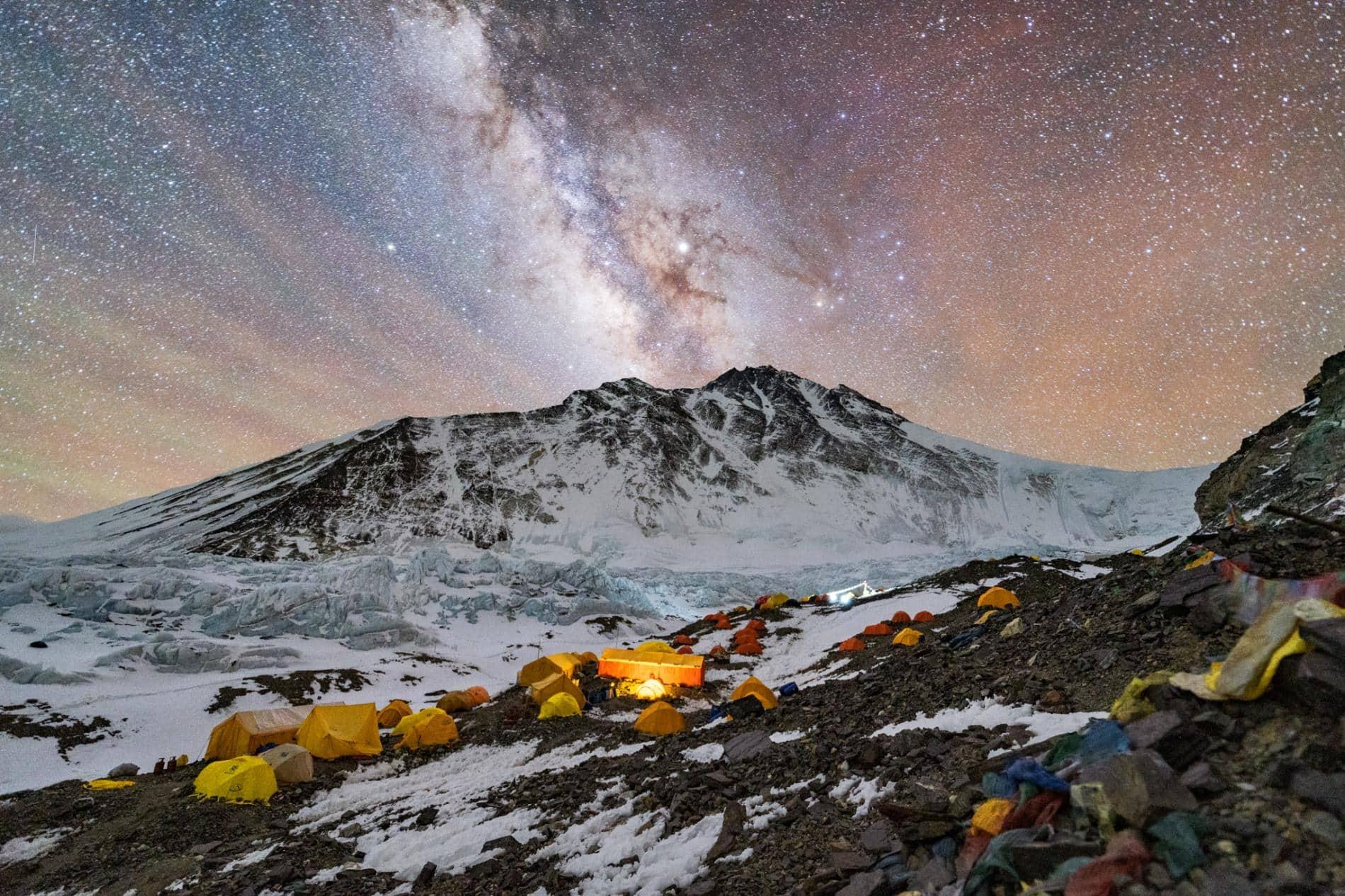 Iz višinskega baznega tabora, kjer je na pol kilometra ledeniške morene raztresenih več kot 200 ljudi, je vrh najvišje gore na svetu videti oddaljen kot Rimska cesta. Vrh Everesta je skrajno desni vrh, ki je komaj viden za zasneženim Severnim sedlom (na desni).